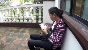 Lady With Mobile Phone Text Messaging at church corridor. San Pablo City, Laguna, Philippines – December 12, 2016: Lady With Mobile Phone Text Messaging at stock footage