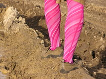 Lady in mud. Young girl in pink tights walking in mud Royalty Free Stock Image
