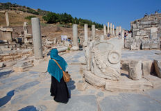 Lady in muslim scarf walking through ruined alley of Greek-Roman city Ephesus Royalty Free Stock Image