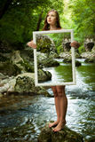 Lady nature - beoutiful young wman stands in nature with a frame Stock Photography