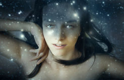 Lady nocturne. Portrait of a beautiful young woman in a fantasy night sky with stars background Royalty Free Stock Photos