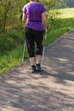 Lady nordic walking in springtime park. With purple black jacket and bright sun shining for happiness exercise royalty free stock image