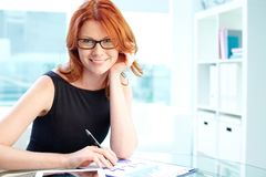 Lady in office. Pretty office lady analyzing financial documents in office Royalty Free Stock Photo