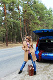 Lady with old suitcase traveling on the road near open blue car trunk. Weekend, traveling by car, road Royalty Free Stock Photo