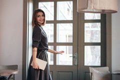 Lady open the door in cafe and holding book. Royalty Free Stock Photos