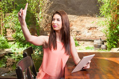 Lady on outdoor terrace holding tablet and ordering Royalty Free Stock Images