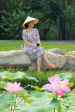 Lady in park. The pretty Chinese lady is sitting in summer garden royalty free stock photo
