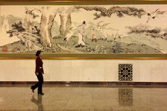 A lady passing by a Chinese painting in the Great Hall of People in Beijing Stock Image