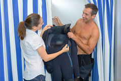 Lady passing man wetsuit to try on Stock Images