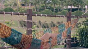 Lady with perfectly tanned long legs relaxes in hammock stock video