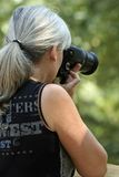 Lady Photographer. Lady taking pictures with Slr Camera Royalty Free Stock Image