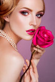 Lady with pink rose. Lady with pink rose and bright makeup Royalty Free Stock Photography
