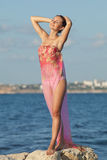 Lady in pink sarong with arms raised on the beach Stock Photos