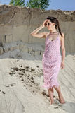 Lady in a pink scaly sundress on sand quarry Royalty Free Stock Photography