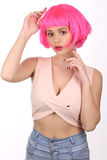 Lady in pink wig touching her head. Close up. White background royalty free stock image