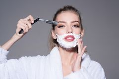 Lady play with sharp blade of straight razor. Girl on dreamy face wears bathrobe, grey background. Woman with face. Covered with foam holds straight razor in royalty free stock photos