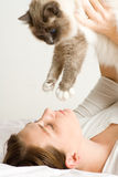 Lady playing with cat in bed Royalty Free Stock Image
