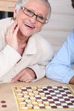 Lady playing checkers with somebody. Royalty Free Stock Photo