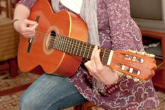 Lady playing guitar. Close up of a young woman playing guitar Stock Image