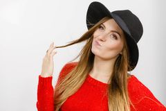 Lady playing with hairs. Fashion headwear clothing fun concept. Lady playing with hairs. Elegant girl wearing fashionable hat twisting her hair rolling it on royalty free stock photography