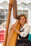 Lady playing a harp Royalty Free Stock Image
