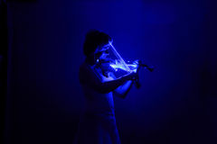 The lady playing music in the dark Royalty Free Stock Image