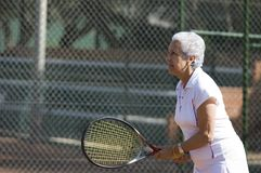 Lady playing tennis. Active attractive senior woman playing tennis in a claycourt Royalty Free Stock Photos