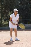 Lady playing tennis. Active attractive senior woman playing tennis in a clay-court Royalty Free Stock Image