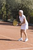 Lady playing tennis. Active attractive senior woman playing tennis in a clay-court Stock Photos