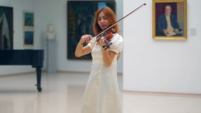 A lady is playing the violin among gallery pictures. 4K stock footage
