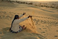 Lady Plying with Smooth Sand Royalty Free Stock Images