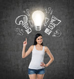 Lady is pointing out the light bulb and drawn question, exclamation marks. Dark concrete background. Royalty Free Stock Images
