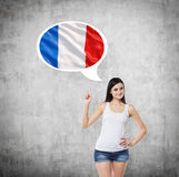 Lady is pointing out the thought bubble with French flag inside. Concrete background. Stock Photos