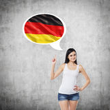 Lady is pointing out the thought bubble with Germany flag inside. Concrete background. Stock Photos