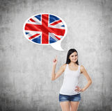 Lady is pointing out the thought bubble with Great Britain flag inside. Concrete background. Stock Photos