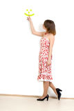 Lady is pointing a smile. On white wall royalty free stock image