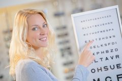 Lady pointing to letters chart at opticians. Acuity stock photography