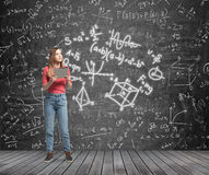 Lady is pondering about complicated math problem. Formulas and graphs are drawn on the black chalk wall. Royalty Free Stock Photography