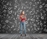 Lady is pondering about education. Educational icons are drawn on the black chalk wall. Royalty Free Stock Image