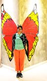 Lady posing in front of a wall art appearing like butterfly with royalty free stock photos