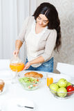 Lady pouring out orange juice Royalty Free Stock Photography