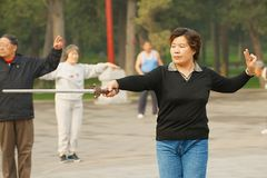Lady practices traditional gymnastics with a sword in Jingshan Park in Beijing, China. Royalty Free Stock Photos