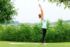 Lady is practicing half moon yoga pose Stock Image