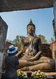 Lady pray sitting Buddha statue in the Ancient temple Thailand Stock Image