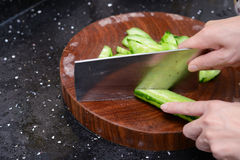 Lady preparing cucumber slices on wooden chop board Stock Image