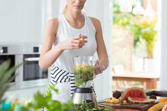 Lady preparing a smoothie. Young lady preparing a healthy smoothie with fresh fruit and vegetables stock image