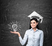 Lady presents a light bulb as a concept of university degree. Graduation hat is drawn above her head. Royalty Free Stock Photography