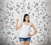 Lady is presents a necessity of higher education. Educational icons are drawn over the concrete background. Stock Photography