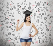 Lady is presents a necessity of higher education. Graduation hat above her head. Educational icons are drawn over the con Stock Images