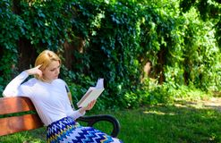 Lady pretty bookworm busy read book outdoors sunny day. Woman concentrated reading book in garden. Girl sit bench. Relaxing with book, green nature background stock photo